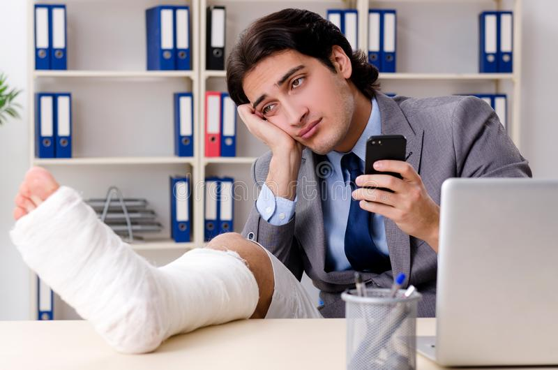 Noga ranił pracownika pracuje w biurze zdjęcia royalty free