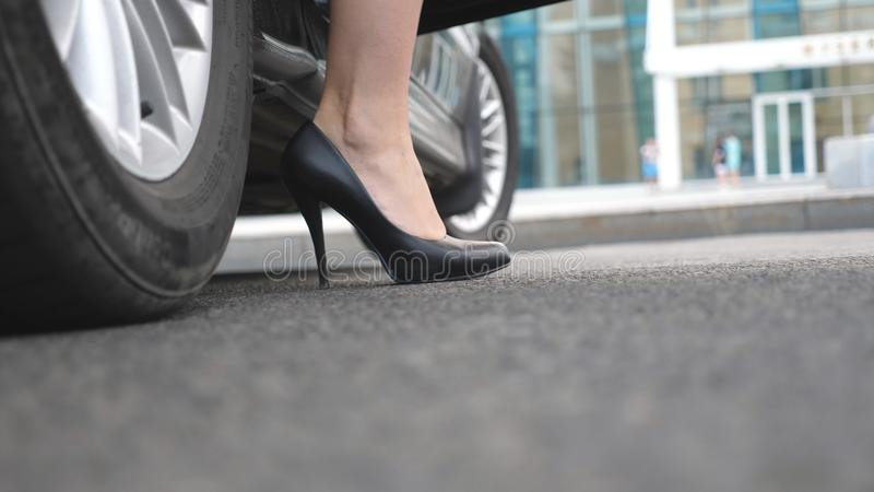 Nogi dostaje z samochodu dziewczyna Biznesowy mężczyzna otwiera samochodowego drzwi dla pięknej młodej kobiety w szpilkach i trzy obrazy stock