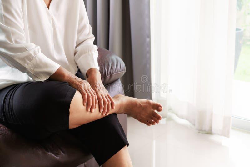Nogi drętwienie, starszy kobiety cierpienie od nogi drętwienia bólu w domu, problemu zdrowotnego pojęcie obraz stock