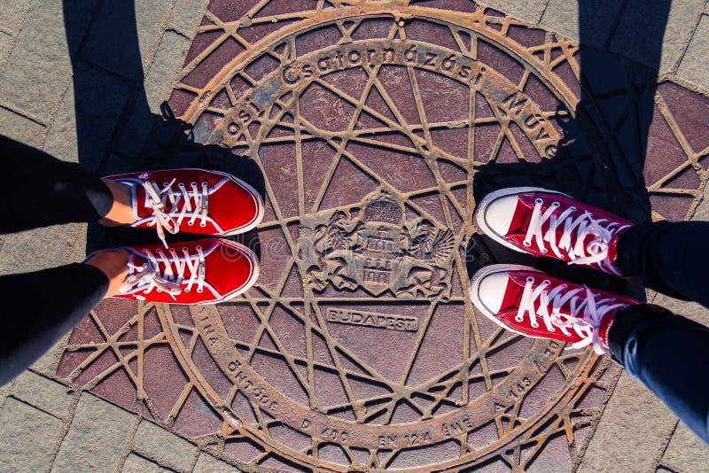 Nogi dwa dziewczyny w czerwonych sportów butach na ulicie na lągu z wpisowym Budapest, zdjęcia royalty free