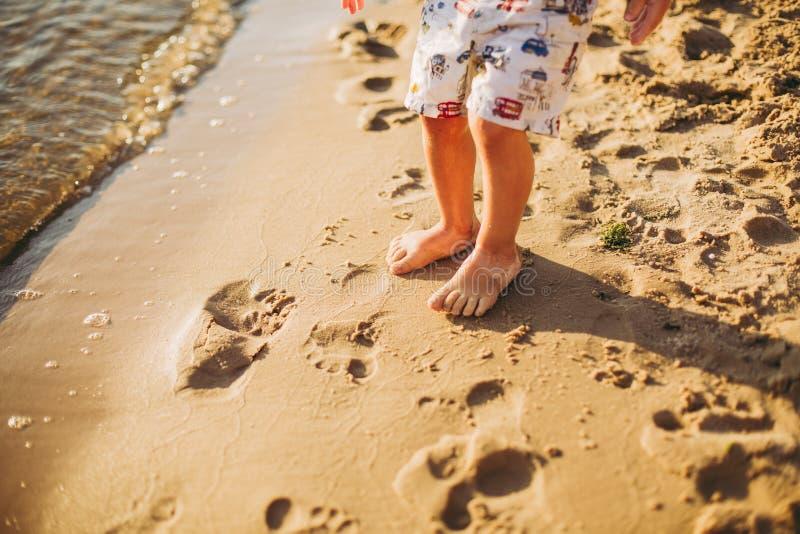 Nogi dziecko stojak na pla?y Dziecko cieki w piasku t?a pi?ki pla?y pi?kna pusta lato siatk?wka Lato wakacji poj?cie zdjęcie stock