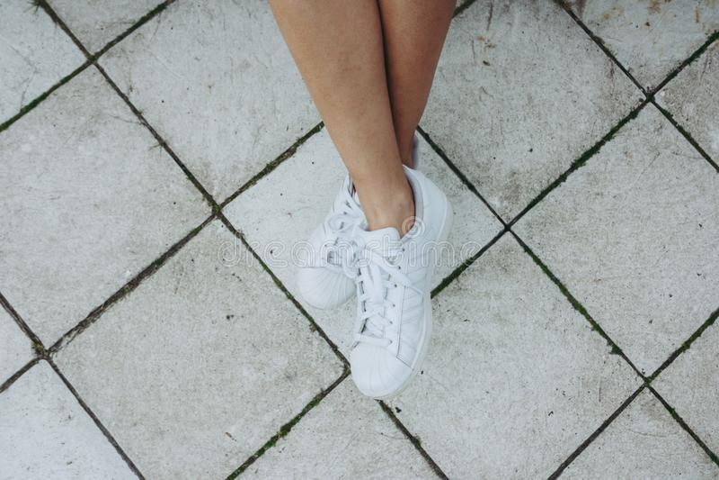 Nogi dziewczyna w białych sneakers na szarości płytce obrazy royalty free