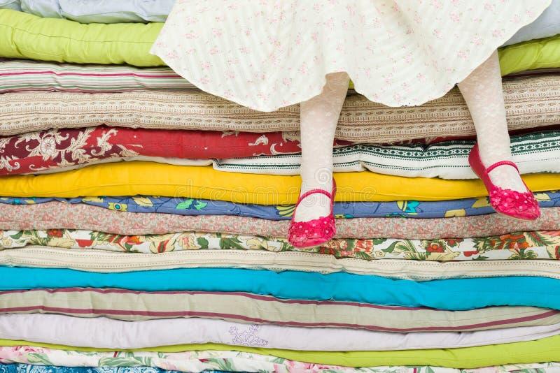 Nogi dziewczyny obsiadanie na stosie kolorowe materac troszkę Dekoracje dla bajki princess na grochu fotografia stock