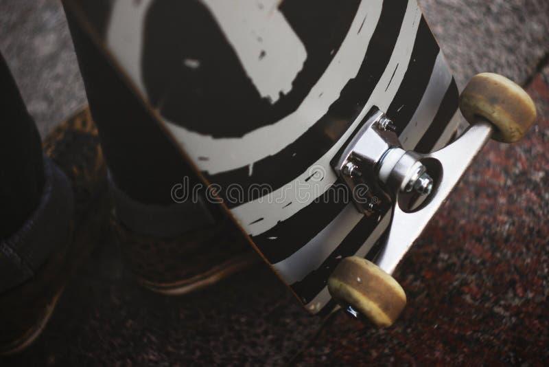 Nogi facet w sneakers z deskorolka na ulicie Zakończenie łyżwowy koło i zawieszenie zdjęcia stock