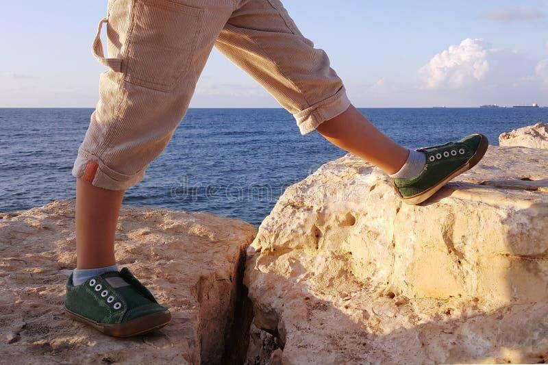 Nogi gigantyczna chłopiec, krok na kamieniach, morze fotografia stock
