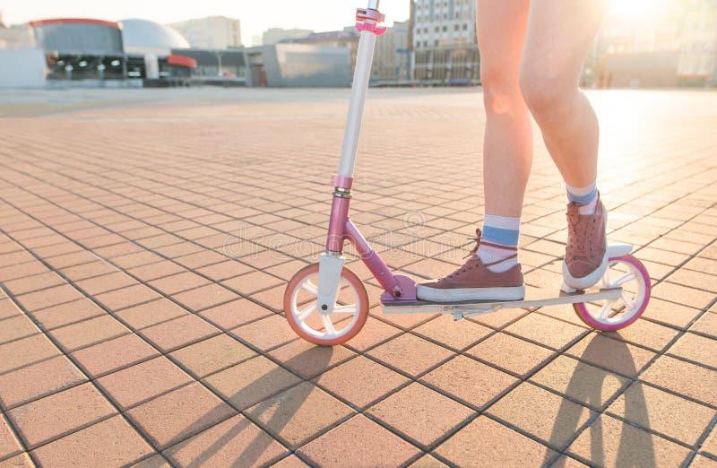 Nogi i menchie kopią hulajnogę na tle zmierzch Dziewczyna jedzie miasto kwadrat na różowej hulajnodze zdjęcie stock