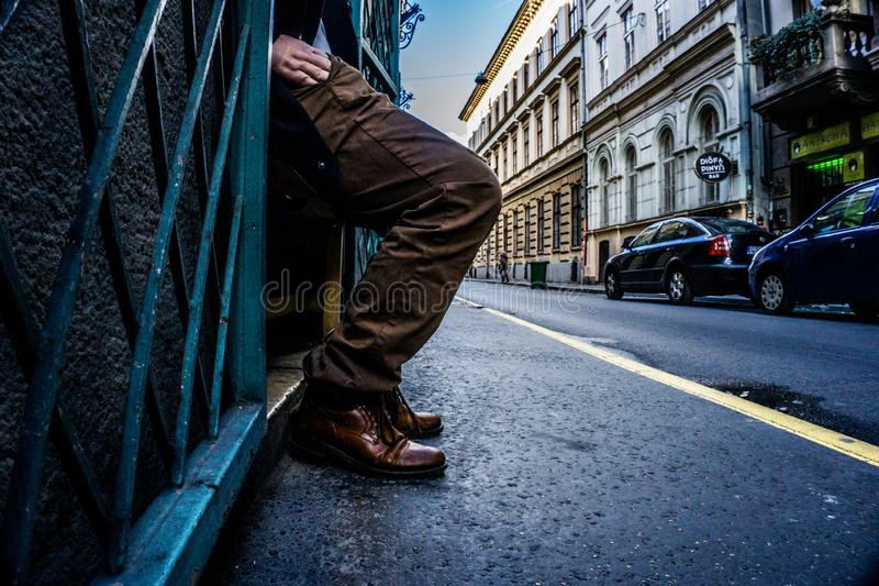 Nogi i ręka mężczyzny dojechanie w jego kieszeń na ulicach Budapest, Węgry z prowadzić linie empasizing akt obraz stock