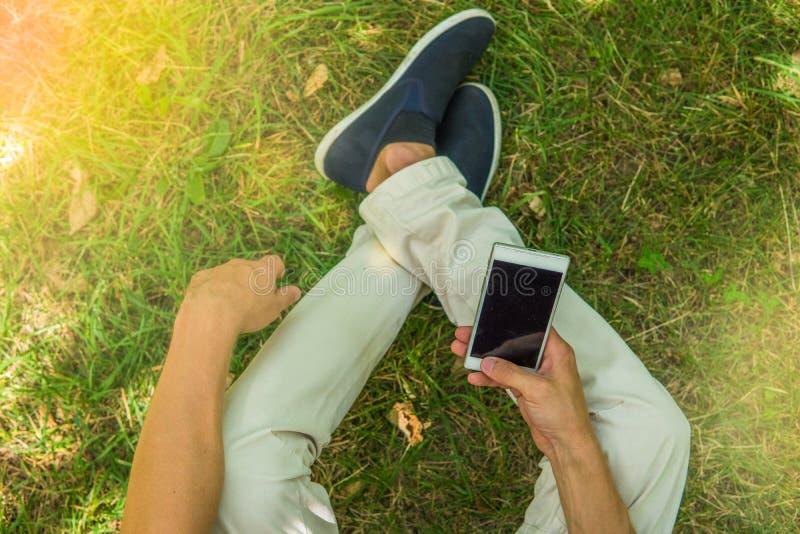 Nogi i telefonu komórkowego odgórny widok Mężczyzna z jego smartphone obsiadaniem obraz royalty free