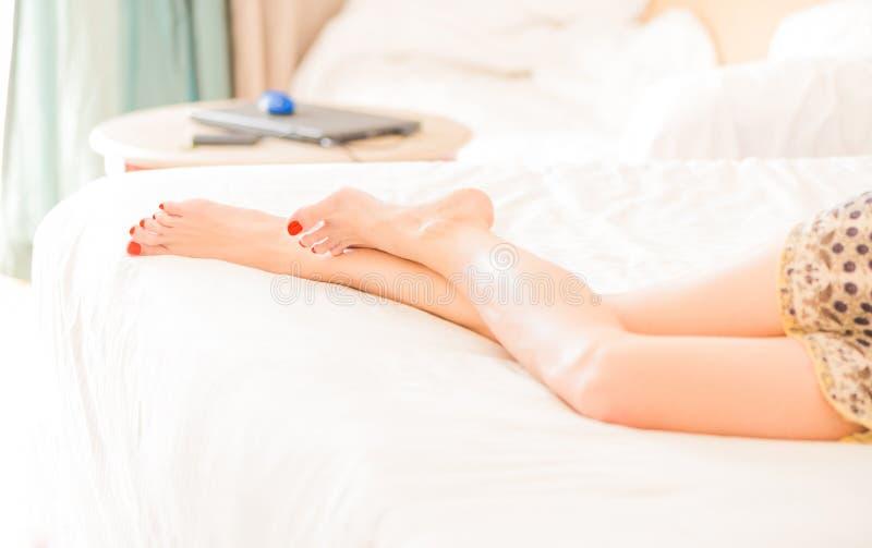 Nogi kłaść na białym łóżkowym prześcieradle kobieta obrazy royalty free