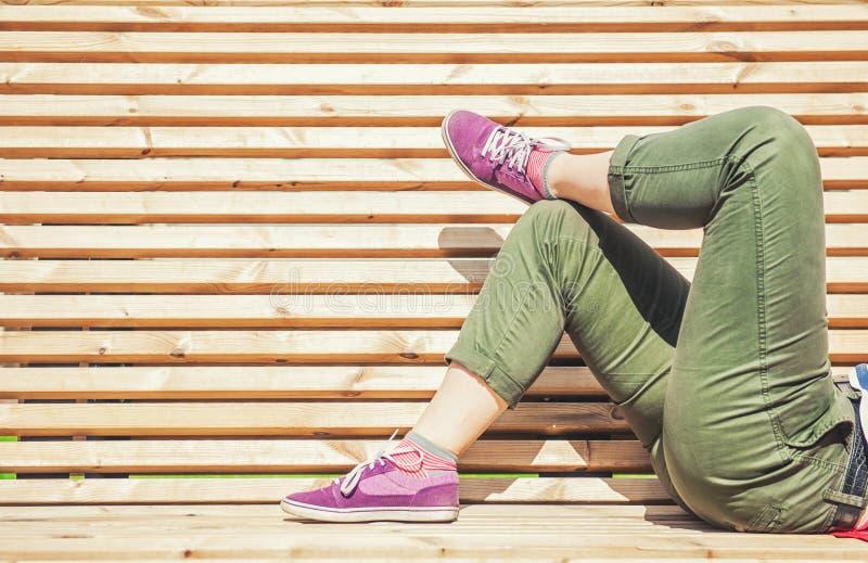 Nogi kobieta kłama na Ben w zielonych spodniach i purpurowy tenisówka obrazy stock