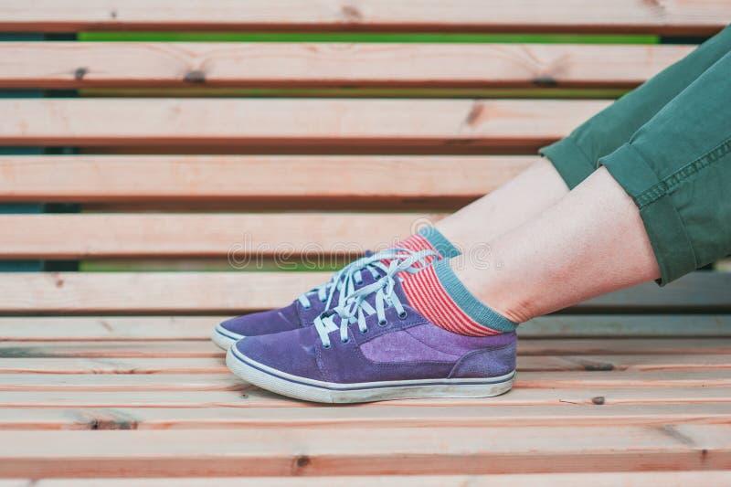 Nogi kobieta w zielonych spodniach i purpurowy tenisówka na ławce zdjęcia royalty free