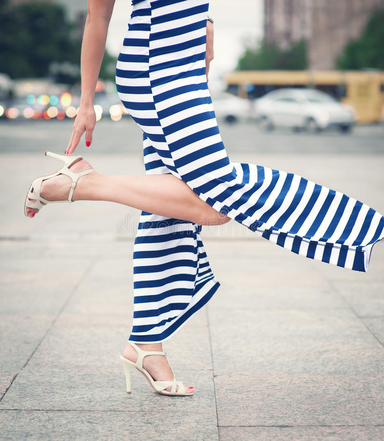 Nogi kobieta z szpilki ubierającą długo paskującą suknią fotografia stock