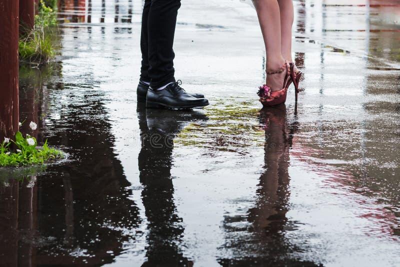 Nogi mężczyzna i kobieta odbijają na mokrym od deszczu drogę zdjęcie royalty free