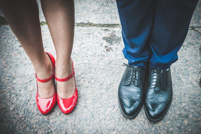 Nogi mężczyzna w czarnych kobietach w czerwonych butach i butach Romantyczny co zdjęcia stock