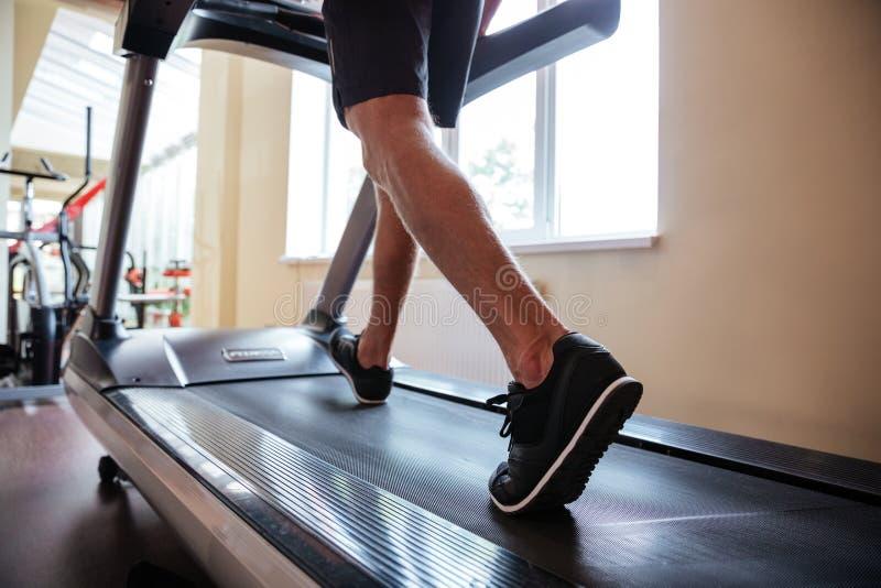 Nogi młody sprawność fizyczna mężczyzna bieg na karuzeli w gym zdjęcia royalty free