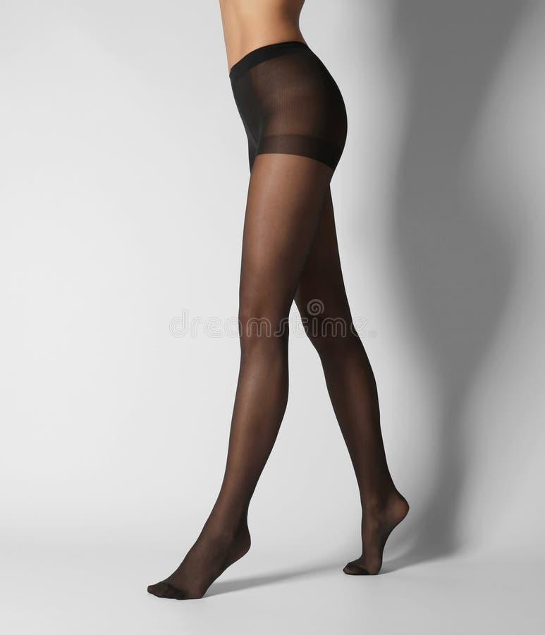 Nogi piękna młoda kobieta w czarnych rajstopy zdjęcia stock