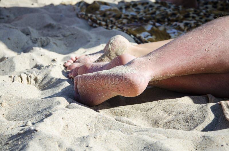 Nogi przy plażą zakrywającą z piaskiem zdjęcia stock