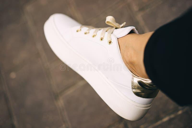 Nogi w białych sneakers z złocistymi koronkami relaks bagaże tła koncepcję czworonożne zakupy białą kobietę koncepcja kulowego fi zdjęcia stock