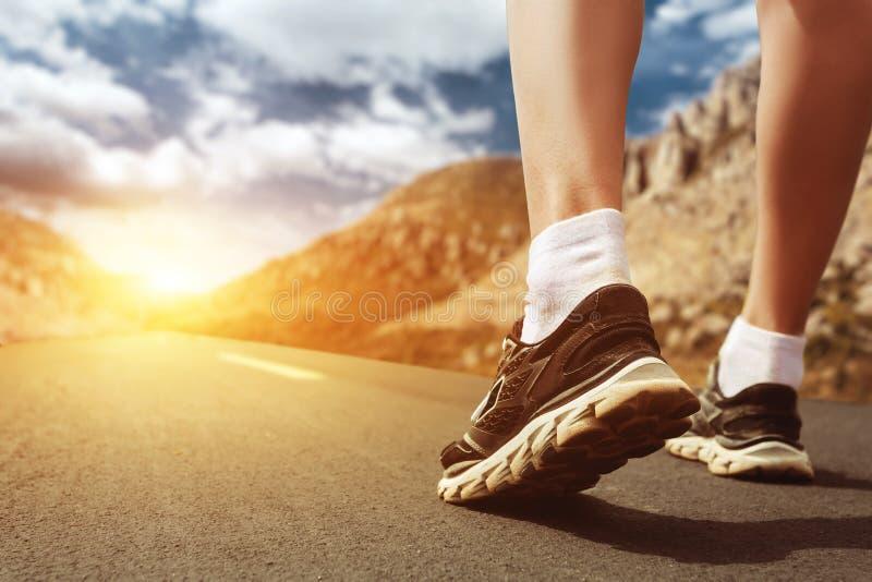 Nogi w sportów butach na drodze przy zmierzchu zbliżeniem zdjęcie stock
