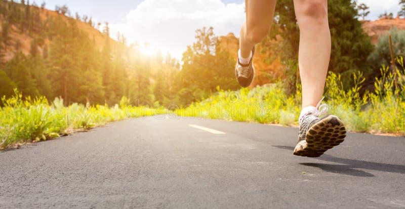 Nogi w sportów butach na drodze przy zmierzchu zbliżeniem zdjęcia royalty free