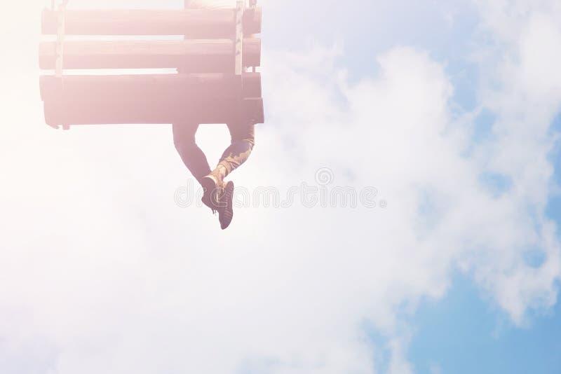 Nogi wiesza w niebach Marzycielka mężczyzna siedzi na huśtawce obraz royalty free