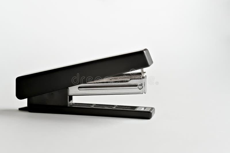 Noir d'agrafeuse avec les trombones d'isolement sur le fond blanc images stock