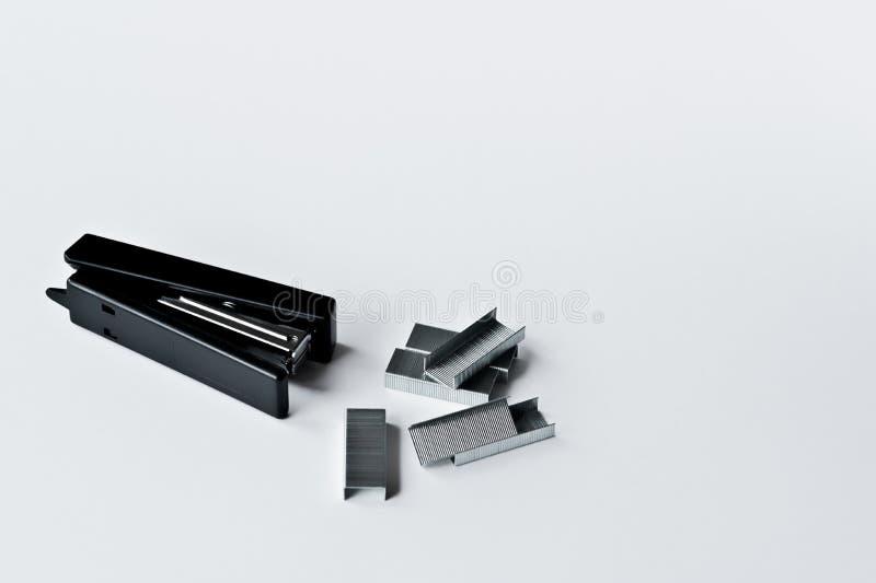 Noir d'agrafeuse avec les trombones d'isolement sur le fond blanc photographie stock