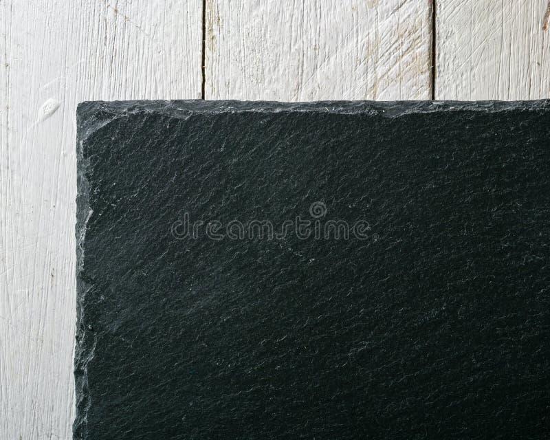 Noir d'ardoise de fond sur le conseil peint par blanc Vue de ci-avant image stock