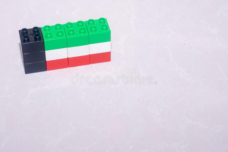 Noir de drapeau du Kowéit, vert, blanc et rouge fait de blocs de jouet sur une tuile avec une réflexion et un espace pour ajouter photographie stock