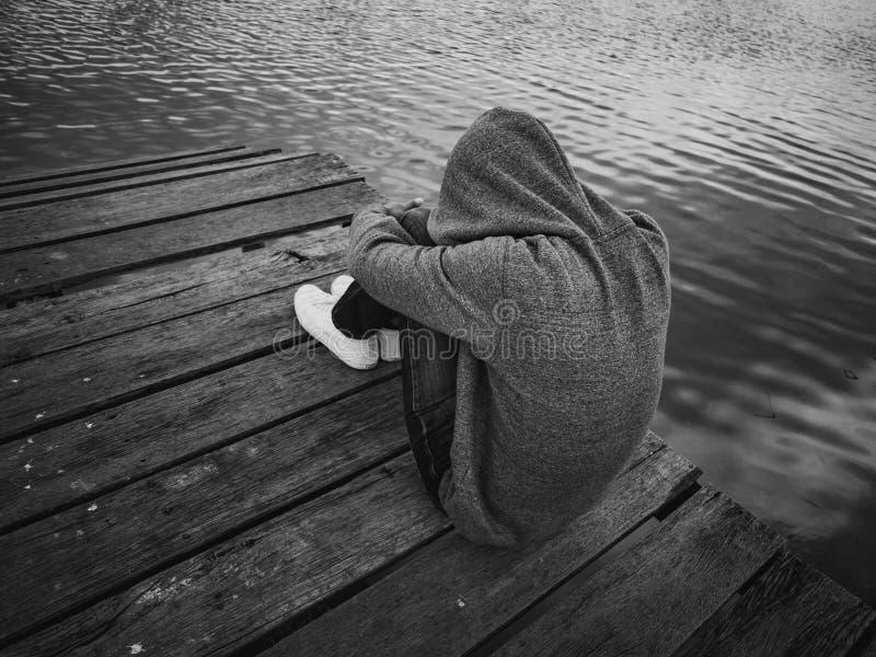 Noir et blanc l'homme s'asseyant sur un pilier près du lac Seulement, concept isolé et triste image libre de droits