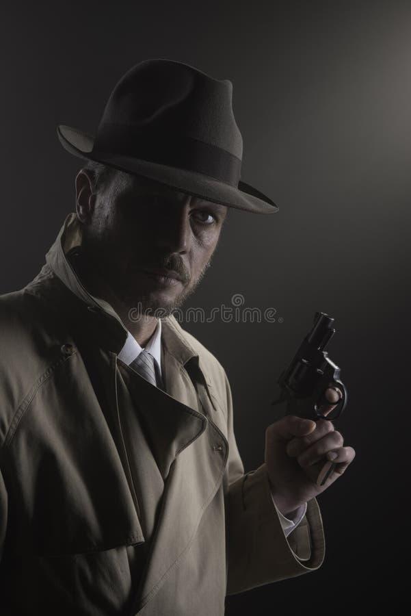 Noir film: kriminalare i mörkret med ett vapen arkivbilder