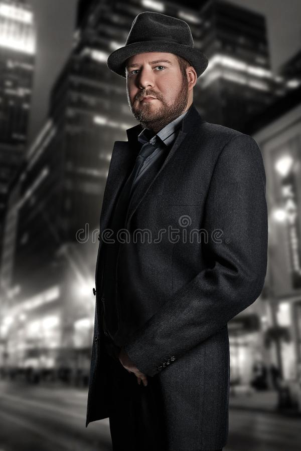 Noir film Retro stilmodestående av en kriminalare En man i en dräkt mot en bakgrund av en nattstad royaltyfri bild