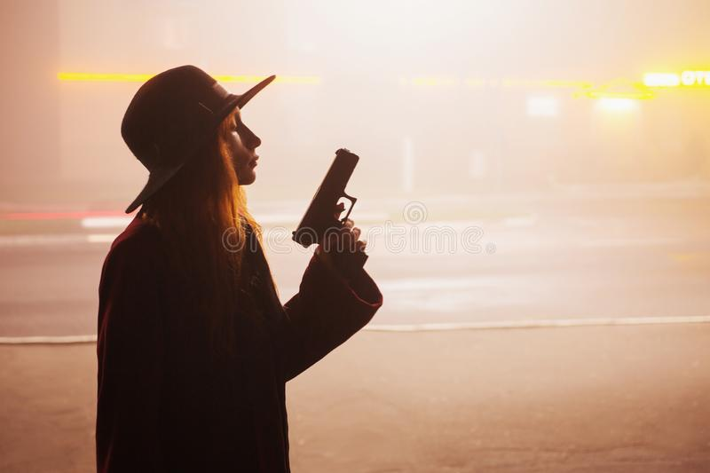 Noir gangster in hat with gun. Woman silhouette on background of night city in fog. Thick mist in dark scary evening city. Dark. Noir silhouette in hat on stock images