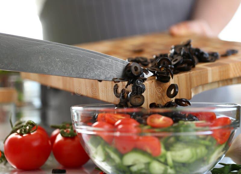 Noir Olive Salad Bowl de Pouring Round Pieces de chef photos stock