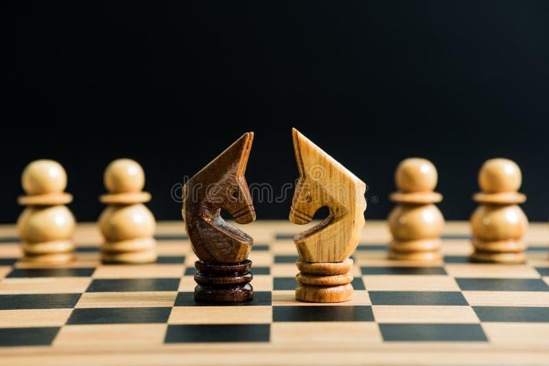 Noircissez contre des pièces d'échecs de chevalier blanc sur l'échiquier photos libres de droits