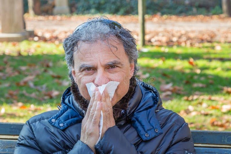 Noircissez en bas de l'homme de veste soufflant son nez avec le tissu photo stock
