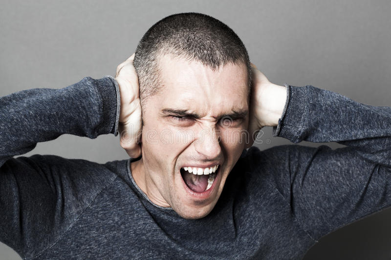 Noise and hearing concept for enraged young man screaming. Noise and hearing concept - enraged young man screaming, plugging his ears to refuse listening to stock photography