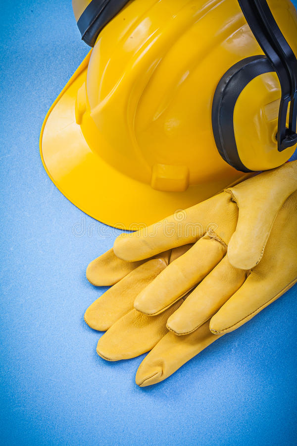 Noise reduction ear muffs safety gloves hard hat on blue backgro. Und construction concept royalty free stock image