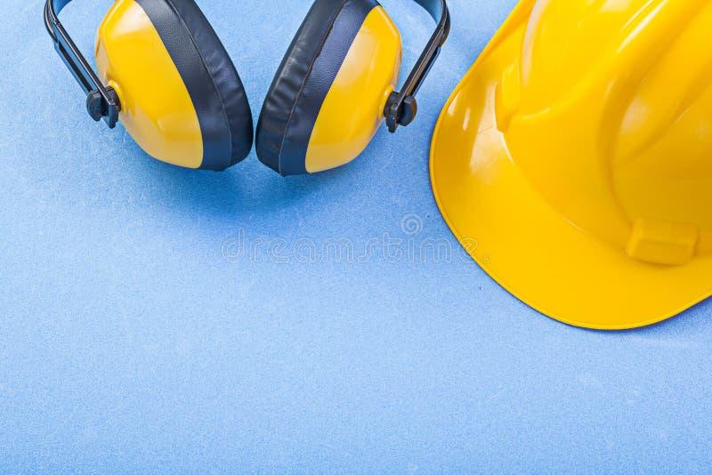Noise reduction earmuffs building helmet on blue background cons. Truction concept stock images