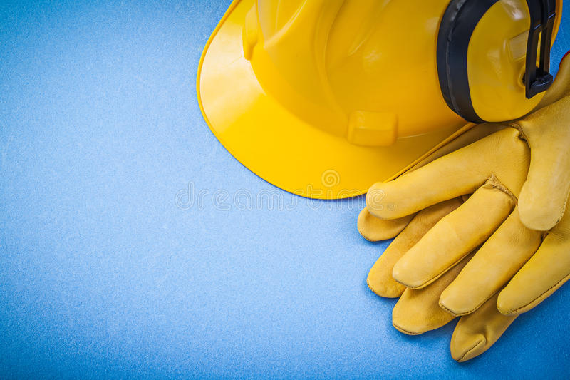 Noise reduction earmuffs protective gloves hard hat on blue back. Ground construction concept royalty free stock image