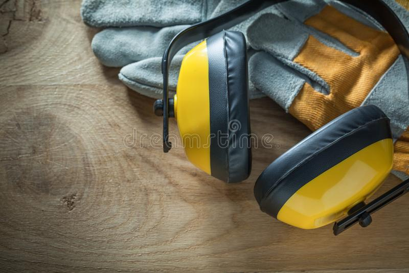 Noise reduction earmuffs protective gloves on wooden board.  royalty free stock image