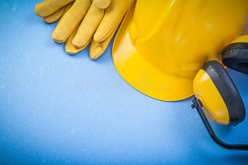 Noise reduction earmuffs safety gloves building helmet on blue b. Ackground construction concept royalty free stock photography
