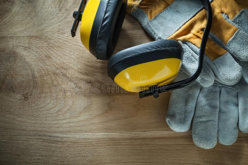 Noise reduction earmuffs safety gloves on wooden board.  royalty free stock photos
