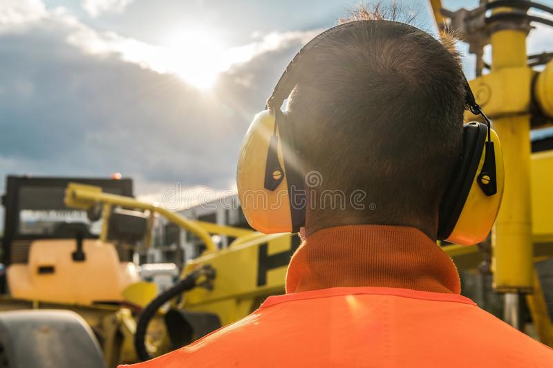 Noise Reduction Equipment. Noise Reduction Construction Equipment. Caucasian Worker with Hearing Protection Headphones stock image