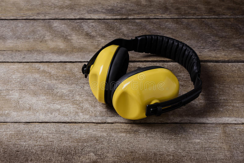 Noise reduction protective earmuffs, Standard construction safety equipment on wooden table. And Light from the window royalty free stock image