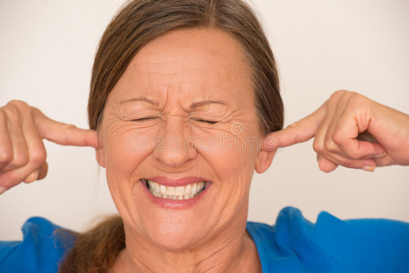 Noise Stressed woman covering ears. Portrait attractive mature woman covering noise from ears with finger, stressed facial expression, closed eyes, isolated stock photography
