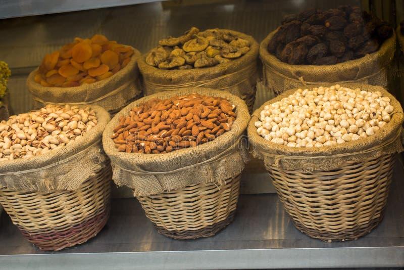 Noisettes, amandes, pistaches, dates, figues, abricots dans les paniers photographie stock