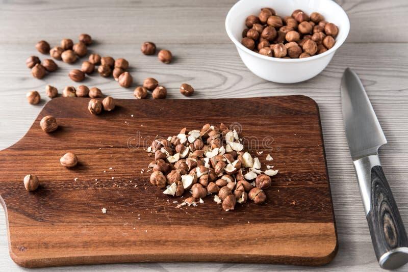 Noisettes coupées sur un conseil en bois avec un couteau, ingrédients pour la cuisson images stock