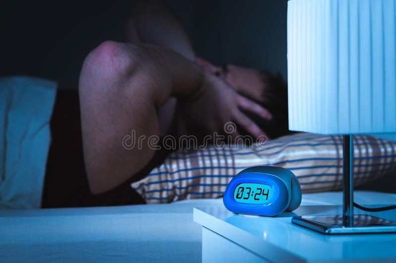 Noisy neighbors or loud party next door. Late in the middle of the night. Man holding and covering ears while trying to sleep. Tinnitus, otitis or bad stock photo