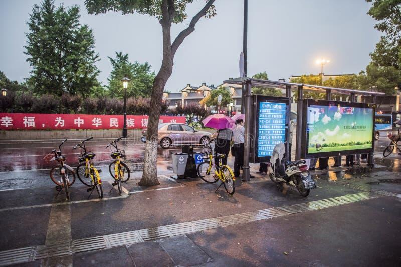 Noite chuvosa, pedestres na parada do ônibus que espera o carro foto de stock royalty free